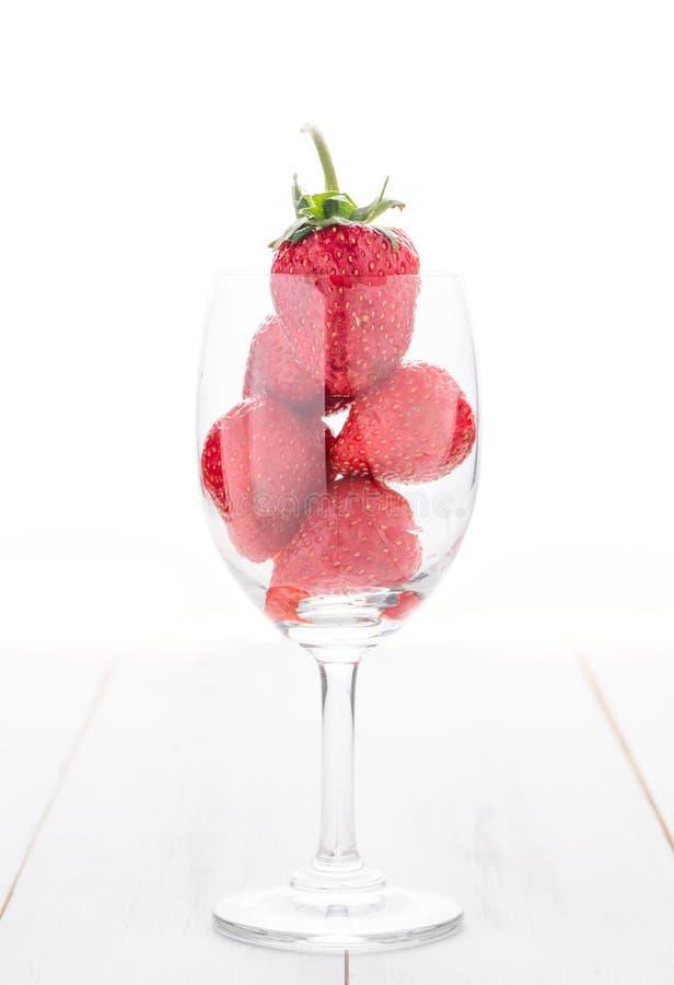 Fragola fresca in vetro di vino isolato su legno bianco immagini stock