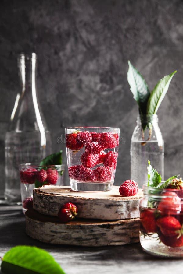 Fragole in acqua su un fondo grigio scuro Alimento sano, frutta Un mazzo dei fiori come decorazione fotografie stock libere da diritti