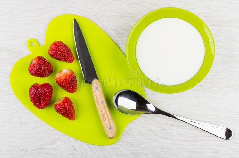 Fragole, coltello sul tagliere, cucchiaio, ciotola con yogurt fotografia stock libera da diritti