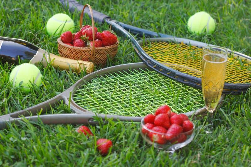 Fragole con panna montata, vetro con champagne e racchette e palle di tennis su erba immagini stock libere da diritti