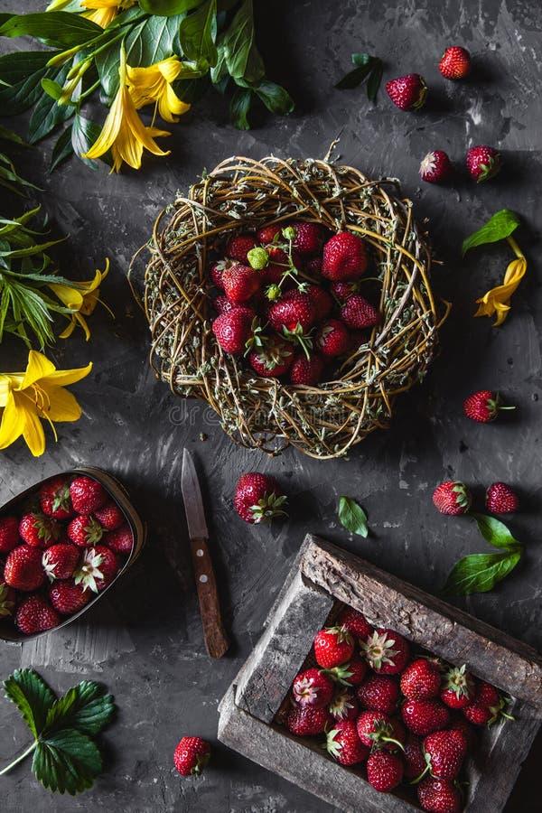 Fragole deliziose con i fiori gialli su un fondo grigio scuro in una corona d'annata Sano immagini stock