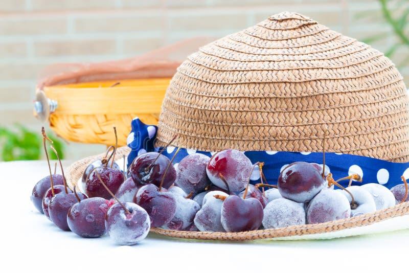 Fragole e cappello congelati bacche sulla tavola bianca immagine stock libera da diritti