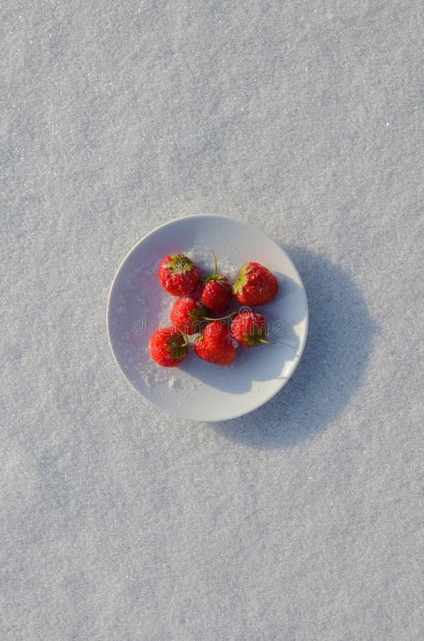 Fragole fresche in un piattino su un fondo bianco di neve immagine stock