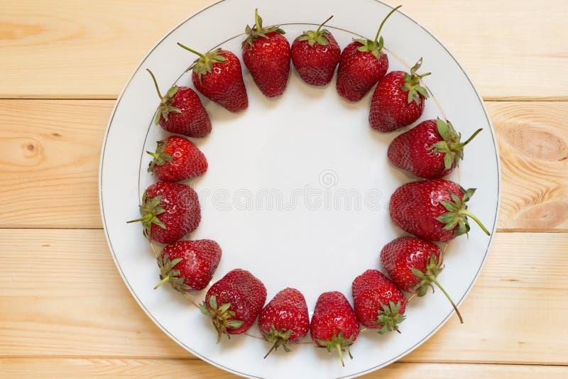 Fragole maturate rosse presentate nella forma del cerchio sul piatto bianco Pagina dalle bacche con lo spazio della copia fotografia stock libera da diritti