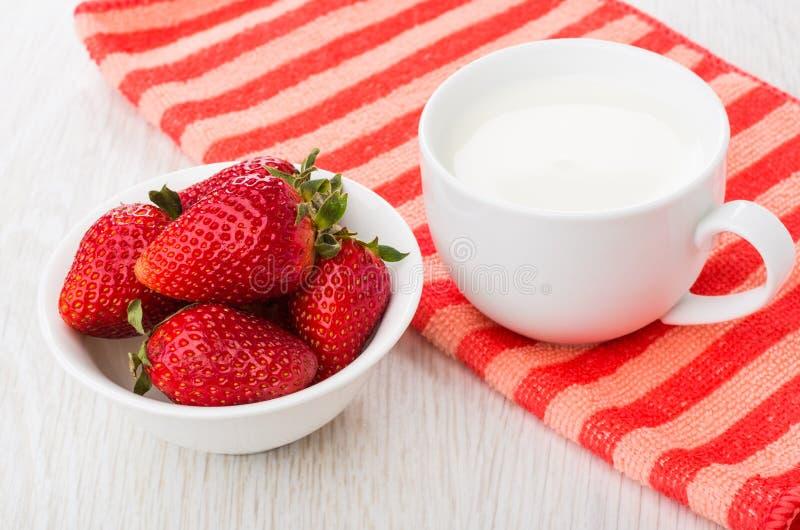 Fragole mature in ciotola, tazza di latte sul tovagliolo rosso fotografie stock libere da diritti