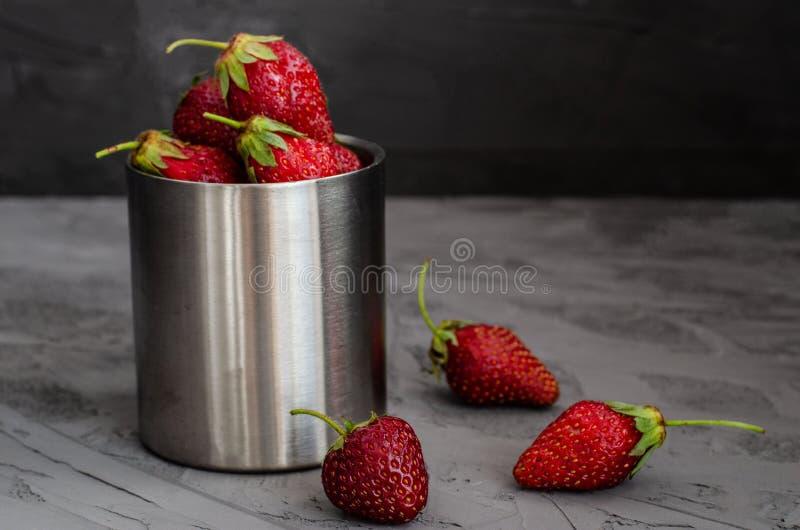 Fragole mature di estate fresca in una tazza su un fondo concreto grigio immagini stock libere da diritti