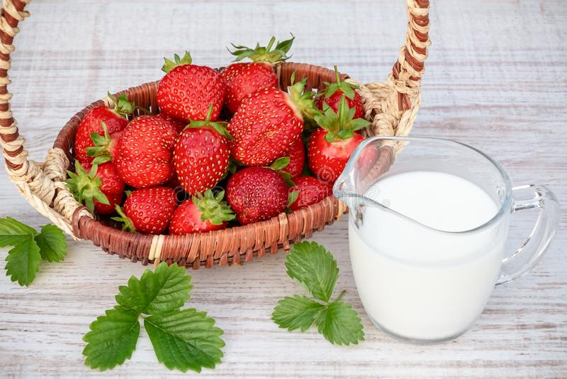 Fragole mature fresche in un canestro e in uno iogurt su una tavola di legno all'aperto un giorno di estate fotografie stock