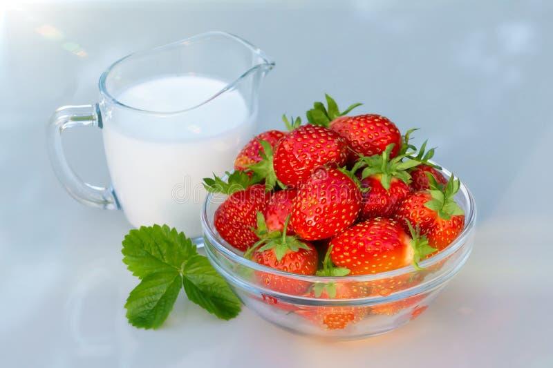 Fragole mature fresche in una ciotola e in uno iogurt su una tavola bianca all'aperto un giorno di estate fotografia stock libera da diritti