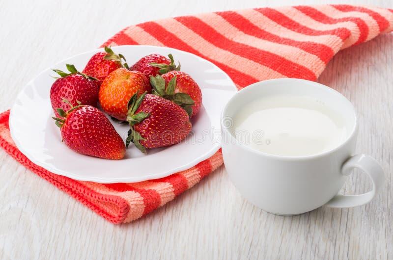 Fragole mature in piatto sul tovagliolo a strisce, tazza di latte fotografia stock libera da diritti