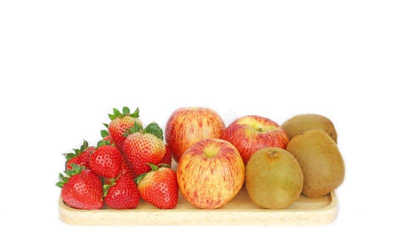 Fragole, mele e kiwi freschi sul piatto di legno isolato su fondo bianco fotografie stock