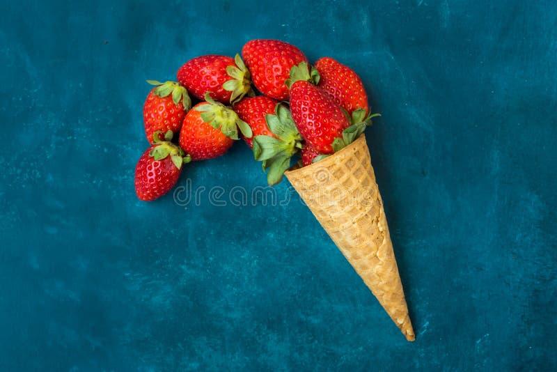 Fragole organiche mature nel cono gelato della cialda, rovesciante imitazione, fondo blu scuro fotografie stock libere da diritti