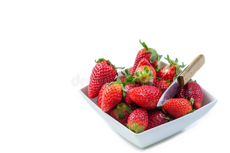 Fragole rosse organiche fresche in una ciotola ceramica su fondo bianco immagine stock libera da diritti