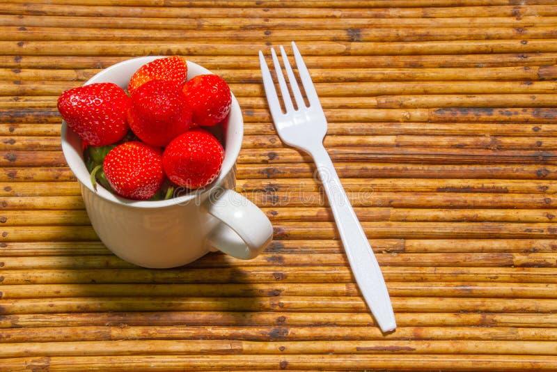 Fragole in tazza, fondo del rattan, fuoco scelto allo strawberri fotografia stock libera da diritti
