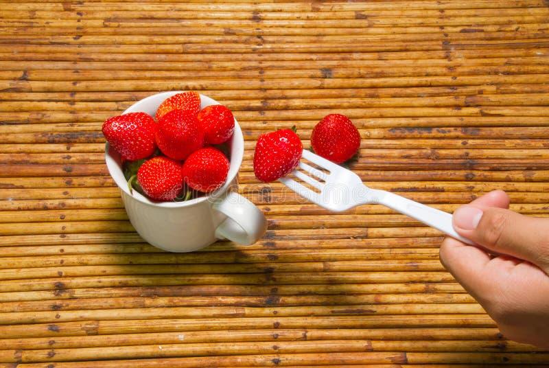 Fragole in tazza, fondo del rattan, fuoco scelto allo strawberri immagini stock