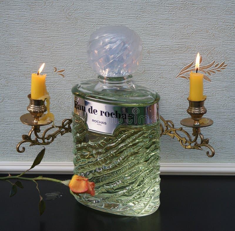 Fragrância de Eau de Rochas para a garrafa de perfume grande das senhoras na frente dos candelabros de um piano com as velas de b imagens de stock