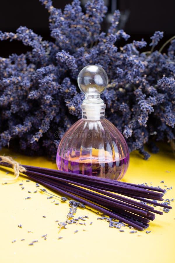 Fragrância saudável natural da aromaterapia e da casa, varas roxas do incenso da alfazema e difusor no fundo amarelo com secado foto de stock