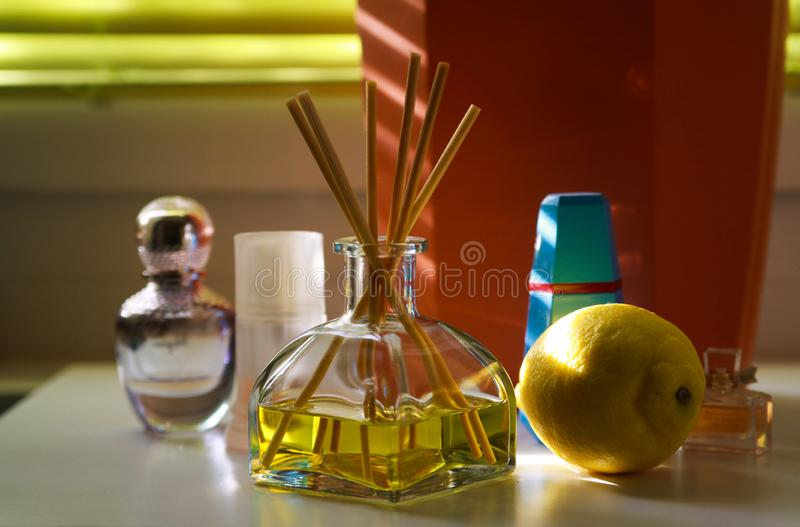 Fragrance diffusor glass with reed sticks between perfume flacons giving natural scent of lemon royalty free stock photo