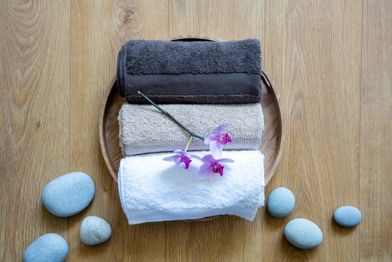 Fragranced ręczniki i ayurveda orchidee nad kamieniami i drewnianym tłem zdjęcie stock