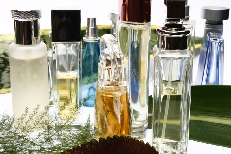 Fragrances and Perfumeries. Bottles with leaves background stock image