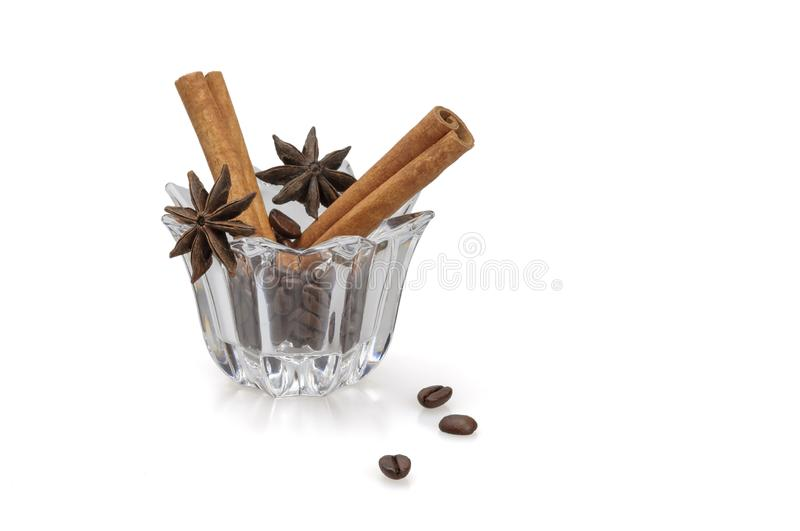 Fragrant cinnamon, star anise and coffee. Cinnamon sticks, star anise star anise and coffee grains in a glass bowl on a white background. Close-up, isolated stock photo