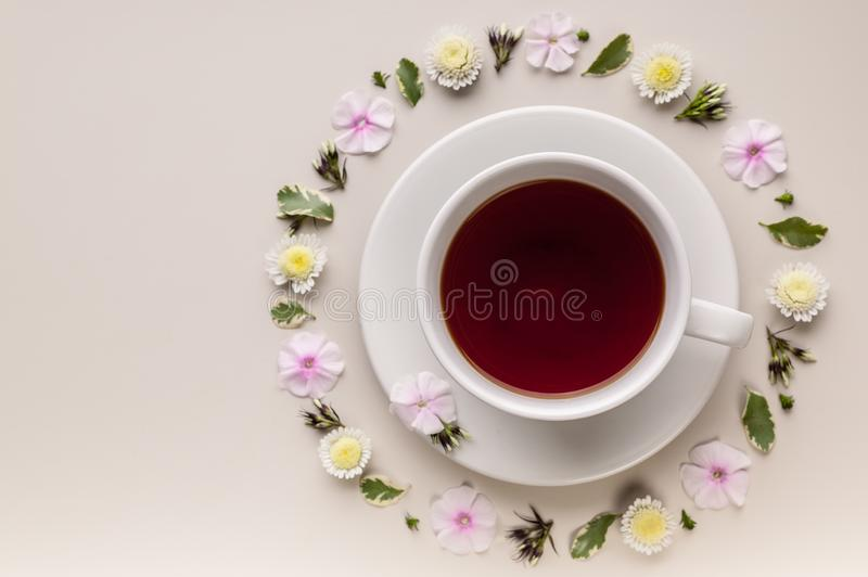 Fragrant herbal tea in a white ceramic cup and saucer. Flower circle pattern on a beige background. Flower tea concept. Tea bag. stock photos