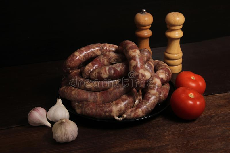 Fragrant homemade german sausage cabbage links with meat grinder lay on a plate on wooden table. Sausage allowed with keto diet royalty free stock image