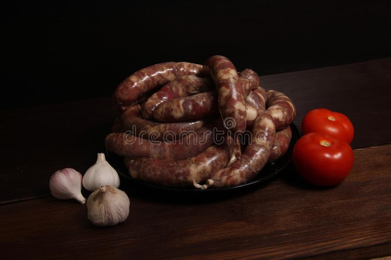 Fragrant homemade german sausage cabbage links with meat grinder lay on a plate on wooden table. Sausage allowed with keto diet.  royalty free stock photo