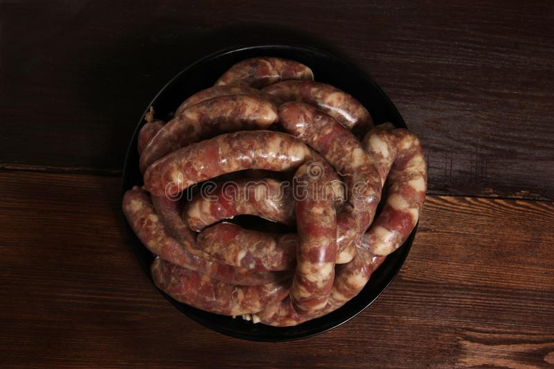 Fragrant homemade german sausage cabbage links with meat grinder lay on a plate on wooden table. Sausage allowed with keto diet. Top view royalty free stock images