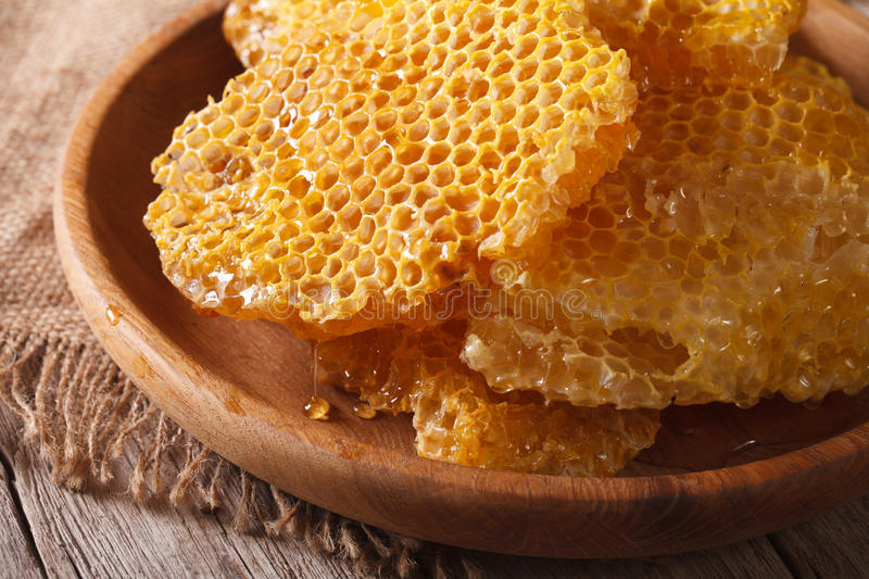 Fragrant honeycomb on wooden plate close up. horizontal. Fragrant honeycombs on a wooden plate on the table close-up. horizontal stock image