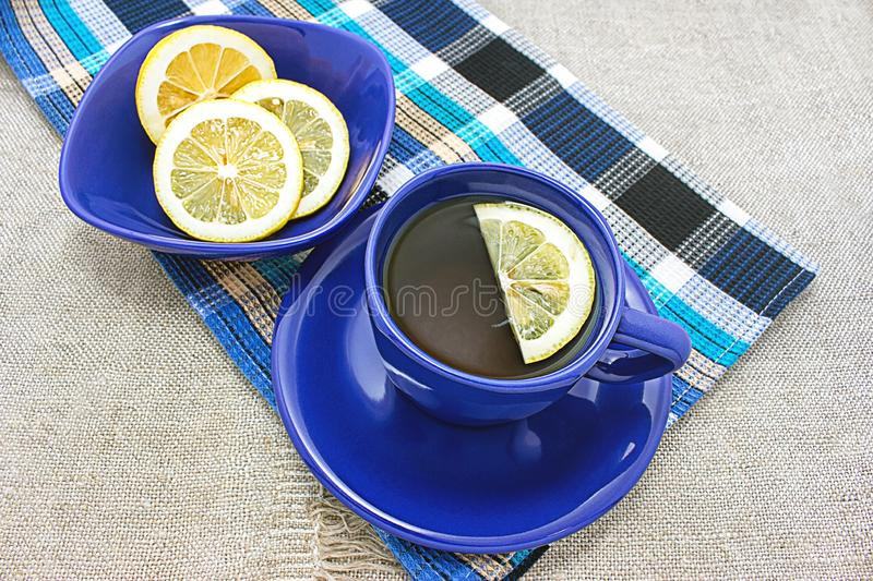 A useful therapeutic drink for colds. Fragrant lemon tea in a blue cup. A useful therapeutic drink for colds stock photography