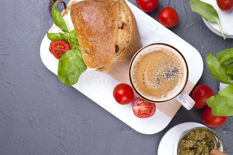 A fragrant morning coffee and a sandwich with mozzarella and basil for breakfast. Tasty and healthy food. Italian lunch. Top view.  stock images