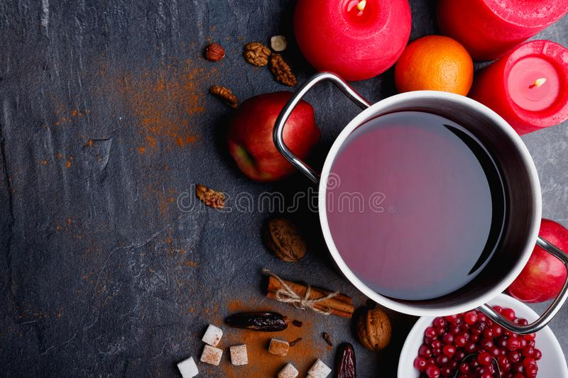 The mulled wine, juicy apple, plate with cranberries, cinnamon and dates and next red burning candles. View from above. royalty free stock images