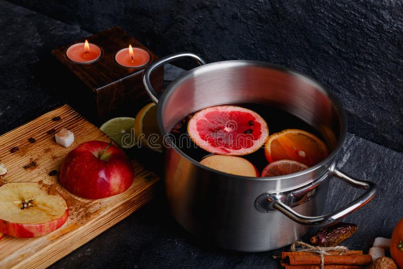 The fragrant mulled wine, next to a board with slices of apples, cinnamon sticks, and decorative burning candles. stock photos