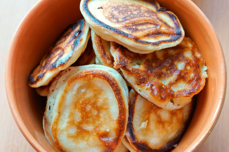 Pancakes in a deep bowl, fragrant pancakes in a plate, round small pancakes in a deep plate stock photography