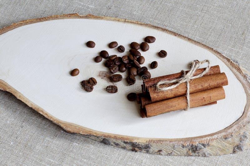 Fragrant piec kawowe fasole i cynamonowi kije wiązali z cienkim jutowym sznurem na drewnianym stojaku Szorstki samodziałowy tło zdjęcie royalty free