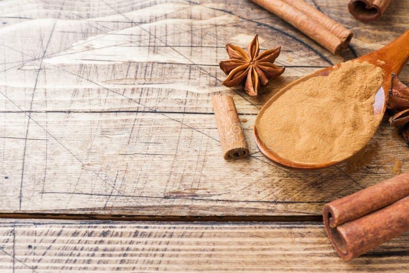 Fragrant pikantność cynamonowi kije i ziemia, gwiazdowy anyż na drewnianej tło kopii przestrzeni zdjęcie stock