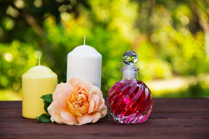 Fragrant rose oil in a beautiful glass bottle. Pink elixir, candles and flowers. Spa concept. Romantic concept. stock photo