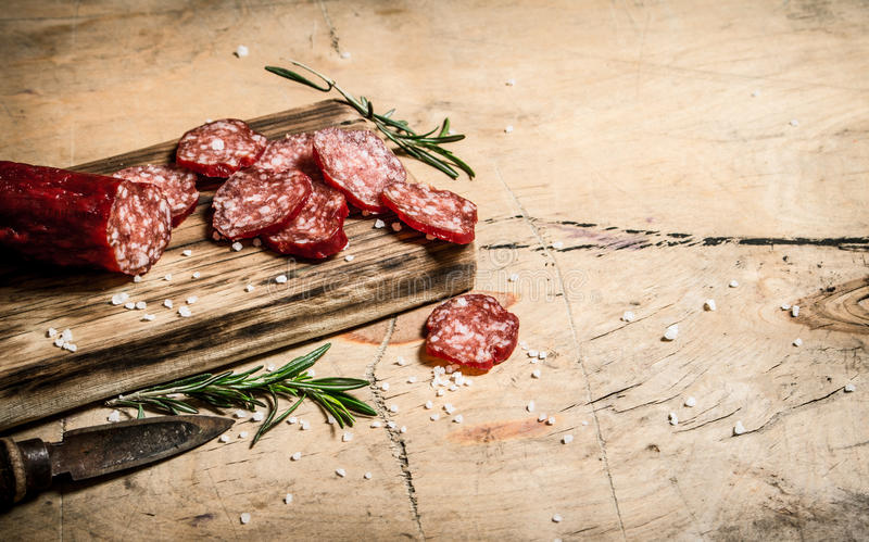 Fragrant salami with rosemary and old knife. On wooden background royalty free stock image