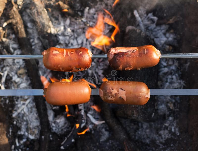 Fragrant sausages fried on a skewer on fire in the garden stock image