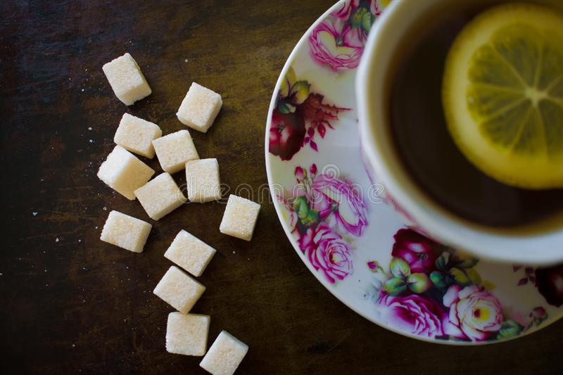 Fragrant tea with a slice of lemon in a bright pink mug, next to thirteen sugar cubes of refined sugar stock images