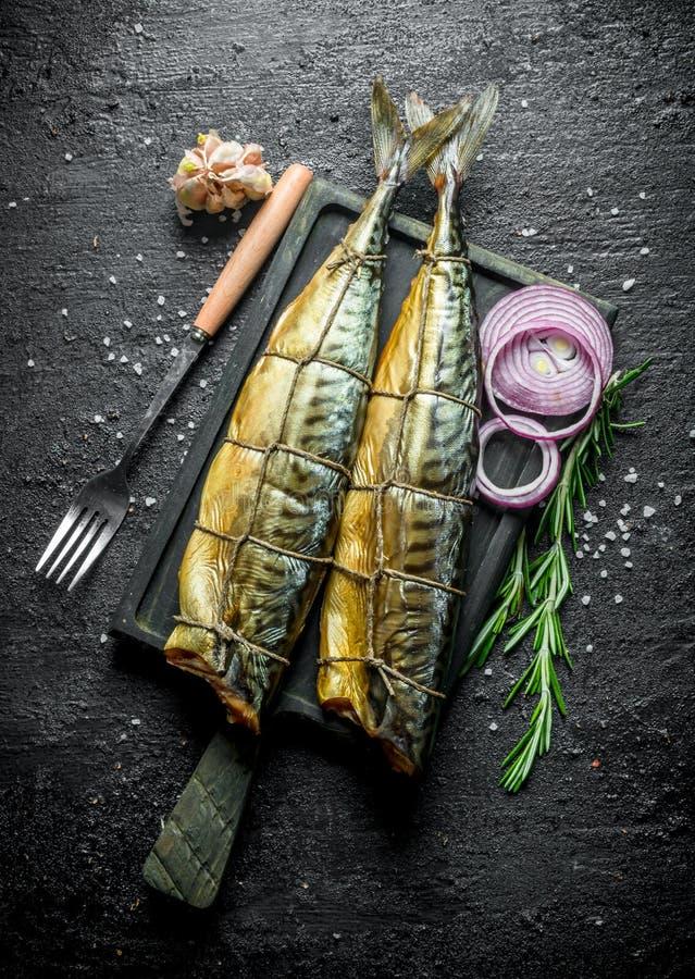 Fragrant uwędzona makrela z siekać cebulami, sprig rozmaryny i czosnek, obrazy royalty free