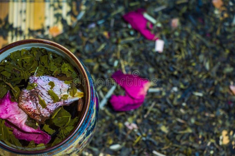 Fragrant zielona herbata z czerwieni róży płatkami warzył w filiżance z ornamentami Chińska kultura obrazy royalty free
