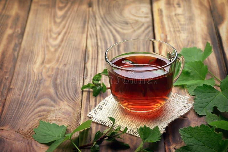 Fragrant ziołowa herbata z nowymi liśćmi, cytryna balsamem, malinkami i rodzynkami, Zakończenie Filiżanka ziołowa herbata na drew zdjęcie royalty free