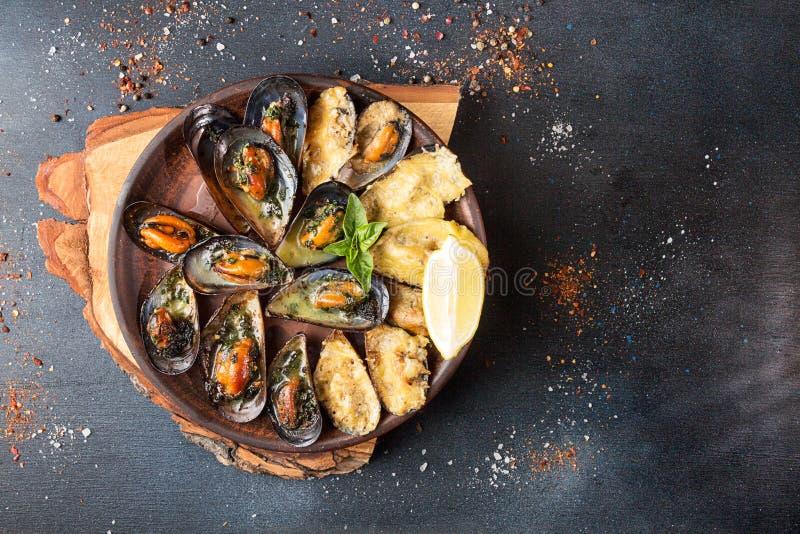 Frais généraux de table de dîner de fruits de mer Grilled a fait des moules cuire au four avec mais photographie stock