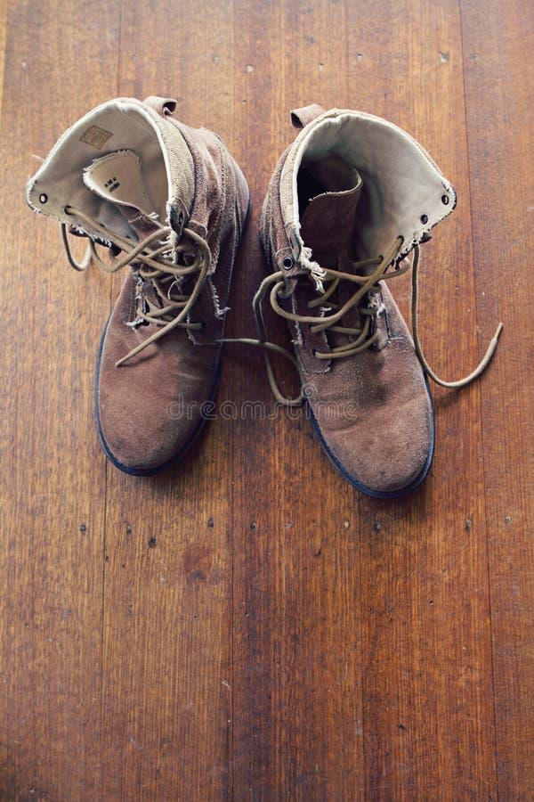 Frais généraux de vieilles bottes usées de travail sur le plancher en bois photo stock
