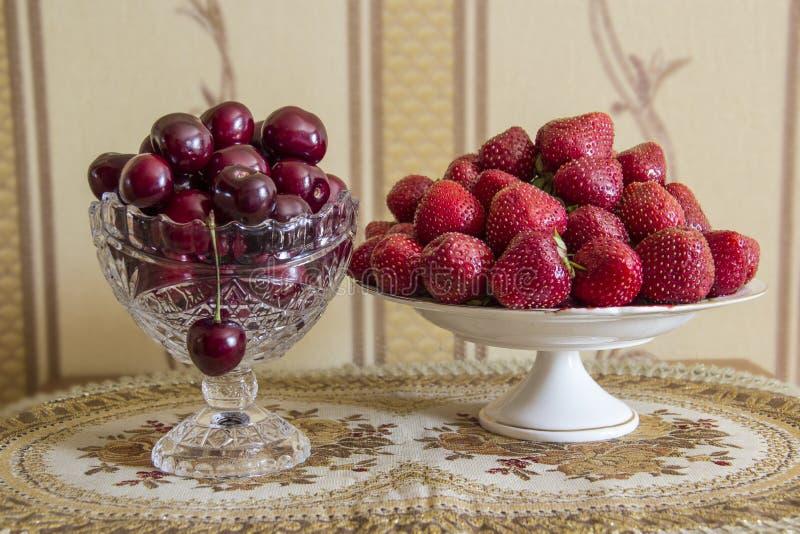 fraise mûre rouge de l'Encore-vie dans un vase et une cerise à porcelaine dans un vase en cristal photo libre de droits