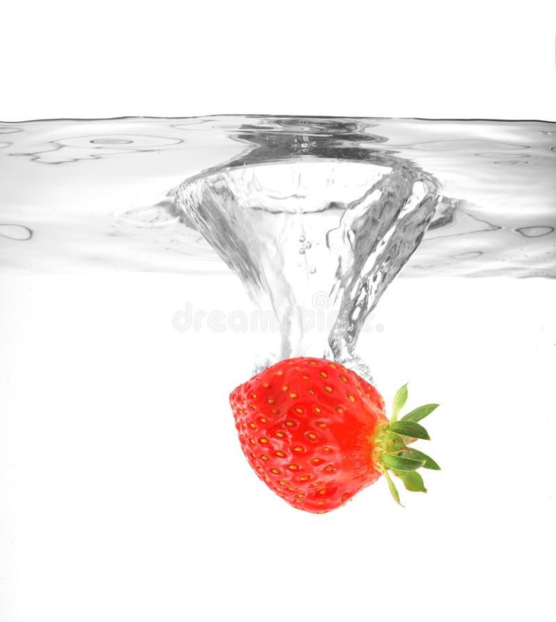 Fraise tombant dans l'eau photographie stock