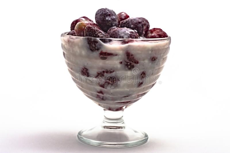 Fraises avec du yaourt dans un vase en verre sur un plan rapproché blanc de fond photos stock