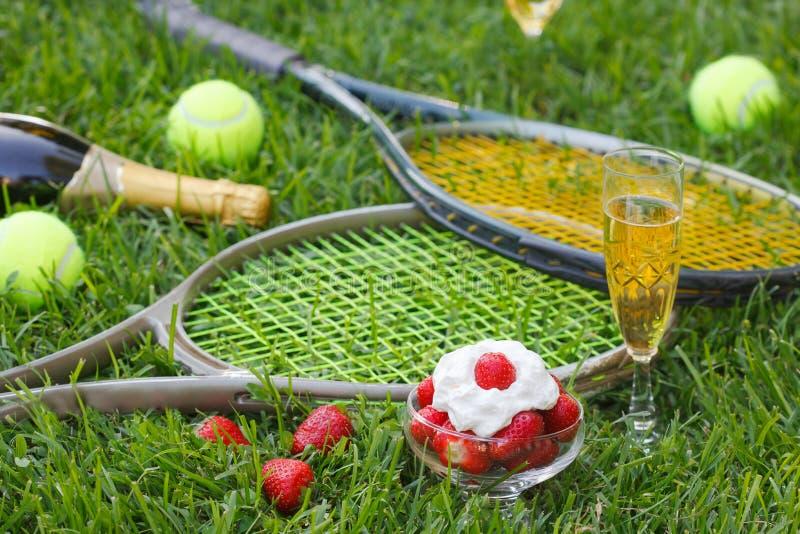 Fraises avec la crème fouettée, le verre avec le champagne et l'équipement de tennis sur l'herbe de tournoi de Wimbledon photos libres de droits