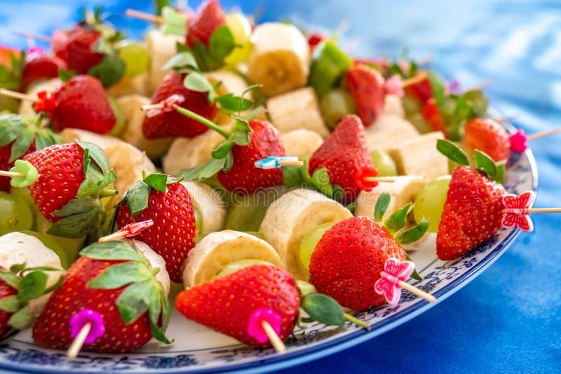 Fraises et d'autres fruits exotiques goupillés avec des bâtons image stock